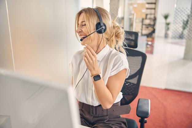 Fröhliche kundendienstmitarbeiterin, die mit computer am tisch sitzt und lacht