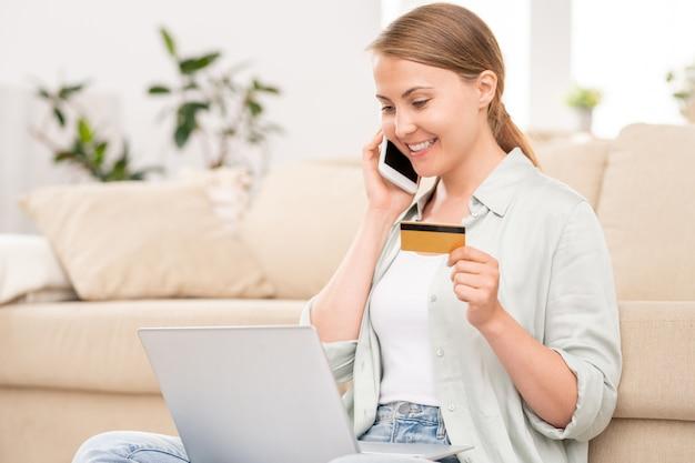 Fröhliche kundin, die mit online-shop-manager spricht, während sie vor laptop sitzt und ordnung macht