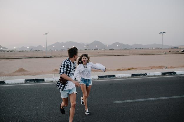 Fröhliche lachende frau, die den rennenden kerl im trendigen hemd und in den jeansshorts einholt. porträt der entzückenden jungen frau, die spaß mit ihrem stilvollen freund am datum im freien hat