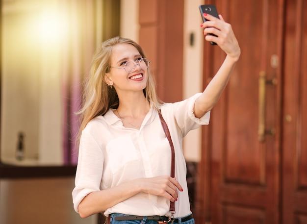 Fröhliche lächelnde blonde frau, die selfie mit smartphone draußen tut