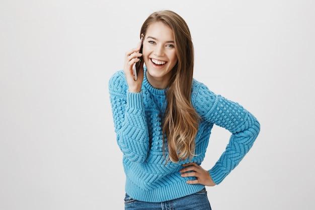 Fröhliche lächelnde frau, die am telefon spricht