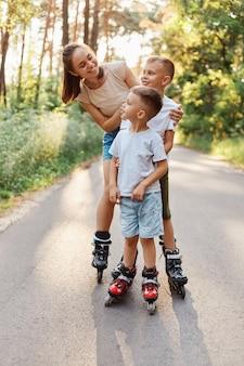 Fröhliche lächelnde frau, die mit ihren kindern im sommerpark rollt, mutter, die kinder mit zahnigem lächeln ansieht, familien-rollerblading und spaß zusammen hat.
