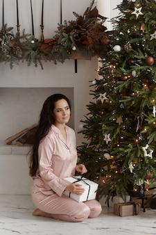 Fröhliche lächelnde frau, die trendige pyjamas trägt, die geschenkbox hält und in der nähe des weihnachtsbaums im gemütlichen zuhause posiert