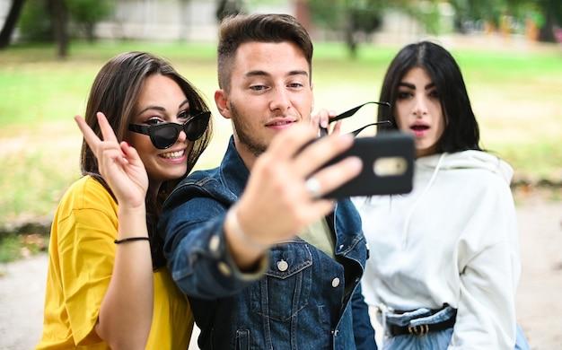 Fröhliche lächelnde freunde im park sitzen auf einer bank und machen selfies mit einem smartphone