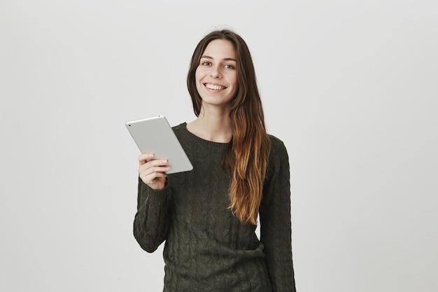Fröhliche lächelnde hübsche frau mit digitaler tablette