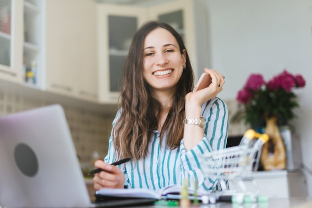 Fröhliche lächelnde junge frau, die kamera betrachtet, arbeit von zu hause aus
