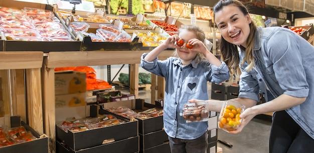 Fröhliche lächelnde junge frau mit kleiner tochter, die globustomaten auf dem markt kauft