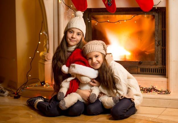 Fröhliche lächelnde mädchen in pullover und mützen, die sich zu weihnachten am kamin aufwärmen