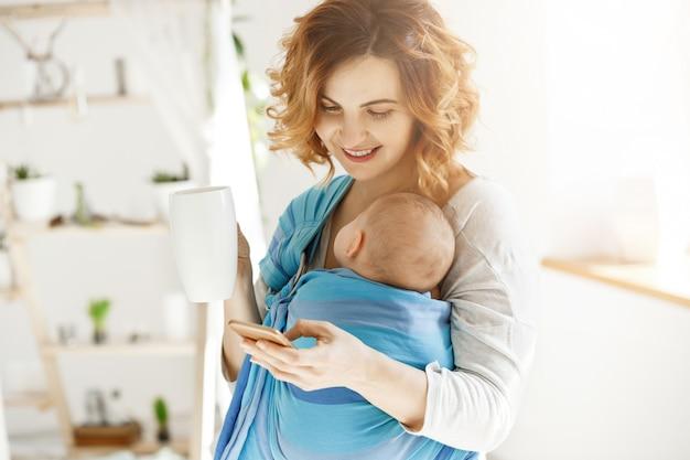 Fröhliche lächelnde mutter trinkt kakao und schreibt ihrem geliebten ehemann eine sms, während kleiner sohn in baby schlank döst. atmosphäre der liebe und des schutzes.
