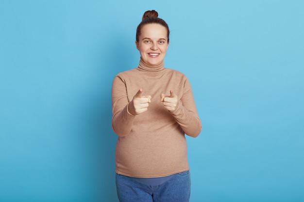 Fröhliche lächelnde schwangere dame, die vorne mit beiden zeigefingern auf blau zeigt