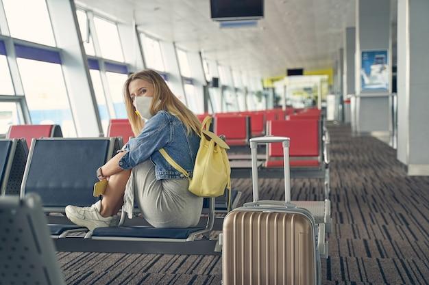 Fröhliche langhaarige frau, die eine schutzmaske trägt, während sie während der quarantänezeit auf reisen geht