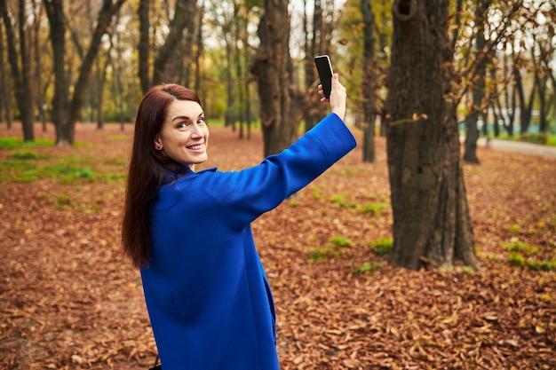Fröhliche langhaarige frau mit ihrem neuen telefon
