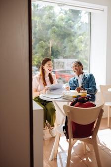 Fröhliche langhaarige weibliche person, die ein lächeln auf ihrem gesicht hält, während sie ihrem gruppenkameraden zuhört