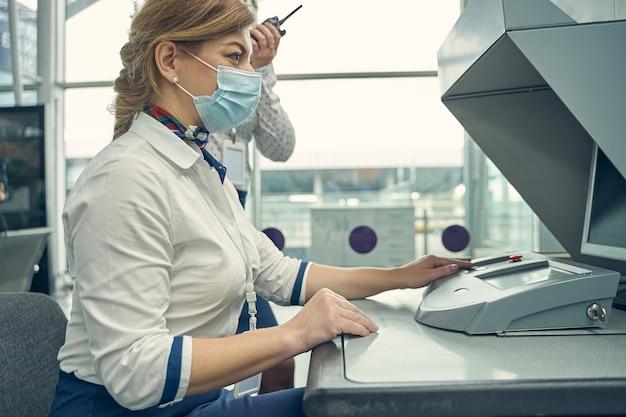 Fröhliche langhaarige weibliche person, die eine medizinische maske trägt, während sie mit passagieren am flughafen arbeitet