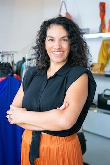 Fröhliche lateinhaarige schwarzhaarige frau, die mit verschränkten armen nahe gestell mit kleidern im kleidergeschäft steht, kamera betrachtet und lächelt. boutique-kunden- oder verkäufer-konzept