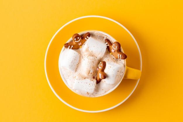 Fröhliche lebkuchenmänner in der gelben tasse latte mit eibisch auf gelber nahaufnahme
