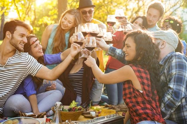 Fröhliche leute, die bei einer grill-picknick-party im freien mit wein essen und jubeln
