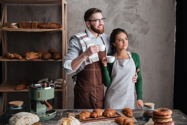 Fröhliche liebevolle paarbäcker, die kaffee trinken. zur seite schauen.