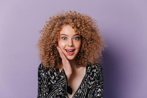 Fröhliche lockige blonde frau im glitzernden disco-oberteil schaut in erstaunen in die kamera auf lila raum.