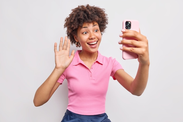 Fröhliche lockige junge afrikanische amerianerin winkt palme in hallo-geste macht videoanruf über smartphonewears lässiges rosa t-shirt genießt online-gespräche isoliert über weißer wand