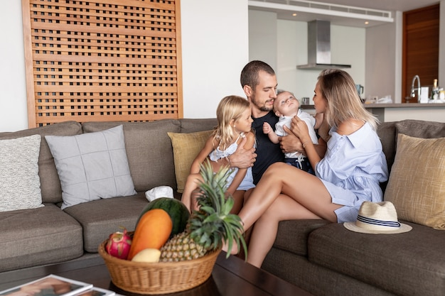 Fröhliche lustige familie junge eltern paar und süße kleine kinder sohn tochter lachend bonding zusammen auf der couch spielen, glückliche mama papa spaß mit kindern kitzeln kuscheln auf dem sofa entspannen