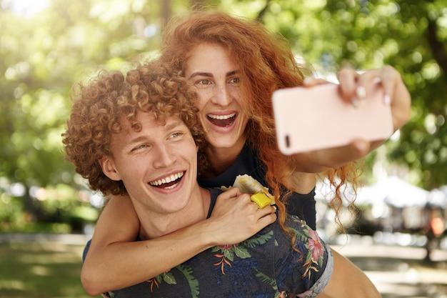 Fröhliche männer und frauen, die sich im freien ausruhen und selfies machen