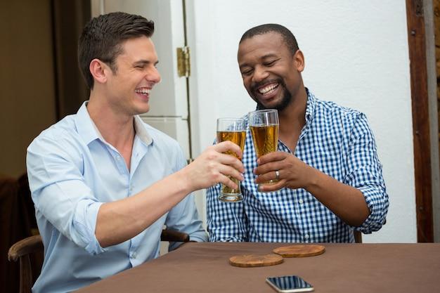 Fröhliche männliche freunde, die biergläser am restauranttisch rösten