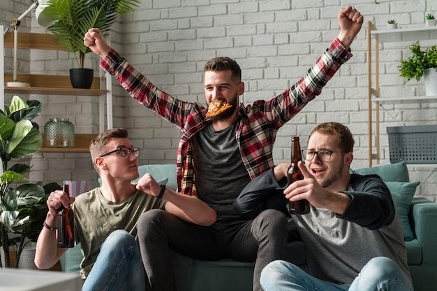 Fröhliche männliche freunde, die pizza haben und sport im fernsehen schauen