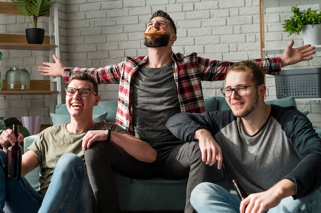 Fröhliche männliche freunde, die pizza und bier haben und sport im fernsehen schauen