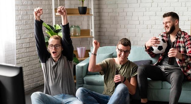 Fröhliche männliche freunde, die sport im fernsehen mit fußball und bier schauen