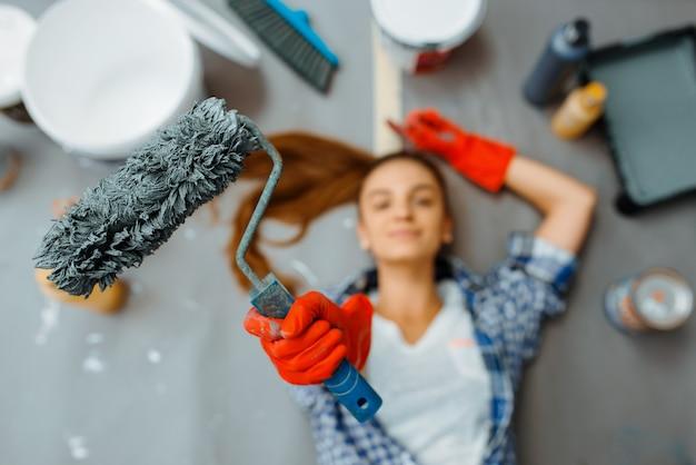Fröhliche malerin liegt auf dem boden, draufsicht. hausreparatur, glückliche frau, die wohnungsrenovierung macht, zimmerdekoration renovieren