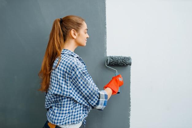 Fröhliche malerin malt wände im innenbereich.