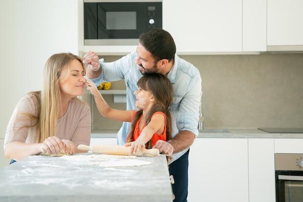 Fröhliche mama, papa und mädchen, die gesichter mit blumenpulver färben, während sie zusammen backen.