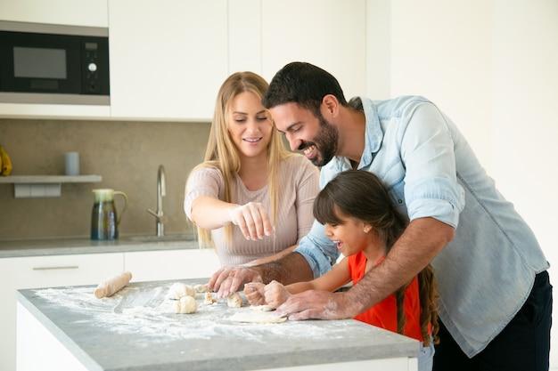 Fröhliche mama und papa lehren tochter, teig auf küchentisch mit mehl unordentlich zu machen. junges paar und ihr mädchen backen brötchen oder kuchen zusammen. familienkochkonzept