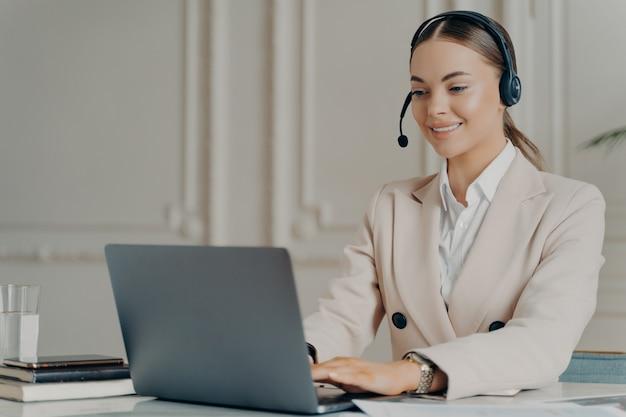 Fröhliche managerin des callcenters, die in einem stilvollen büro sitzt und kunden bei der arbeit am laptop berät, erfolgreiche geschäftsfrau im leichten anzug, die online mit dem projektteam spricht