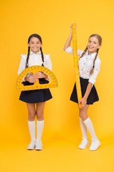 Fröhliche mathematik. stamm disziplinen. zurück zur schule. mathematik und geometrie. kinder in uniform an der gelben wand. freundschaft und schwesternschaft. glückliche kleine mädchen studieren mathematik. schüler verwenden winkelmesser.