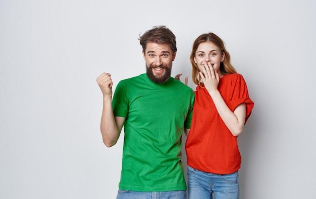 Fröhliche mehrfarbige t-shirts von mann und frau umarmen den lebensstil der freundschaftsgefühle
