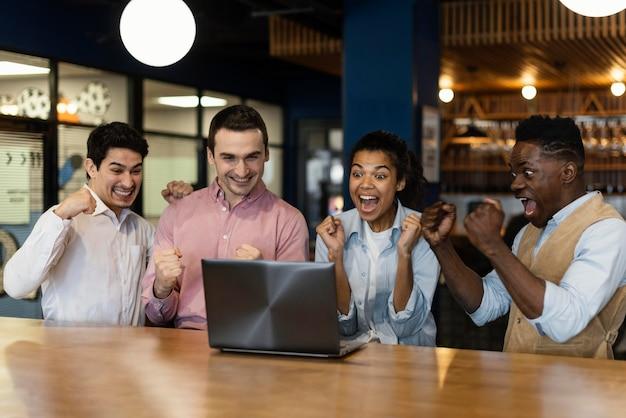 Fröhliche menschen, die während eines videoanrufs bei der arbeit glücklich sind