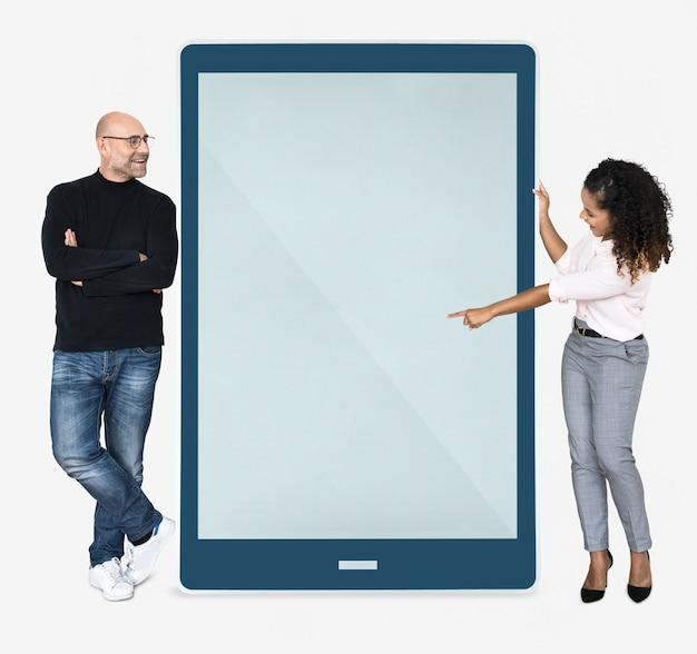 Fröhliche menschen zeigen auf einem tablet-bildschirm
