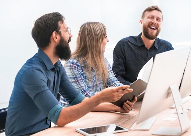 Fröhliche mitarbeiter besprechen etwas bei einem meeting im büro