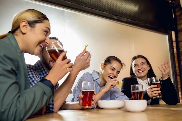 Fröhliche mitarbeiter, die nach einem angespannten arbeitstag ein firmenevent feiern, sehen erfreut freundlich aus