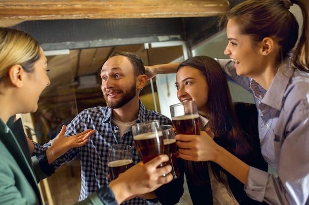 Fröhliche mitarbeiter, die nach einem angespannten arbeitstag ein firmenevent feiern