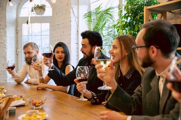 Fröhliche mitarbeiter, die während einer firmenfeier, einer firmenveranstaltung feiern. junge kaukasische leute in geschäftskleidung, die sprechen, wein trinken. konzept der bürokultur, teamwork, freundschaft, urlaub, wochenende.