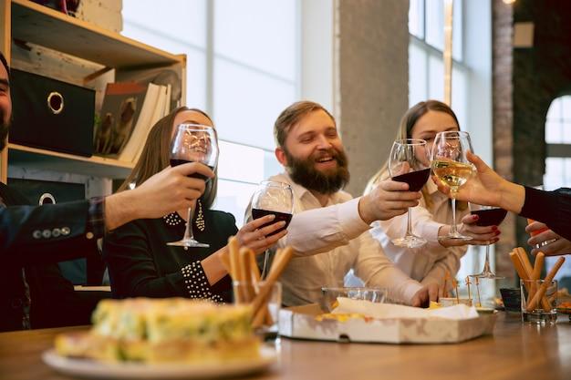 Fröhliche mitarbeiter, die während einer firmenfeier und einer firmenveranstaltung feiern. junge kaukasische leute in geschäftskleidung jubeln, lachen. konzept der bürokultur, teamwork, freundschaft, urlaub, wochenende.
