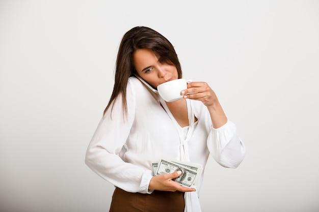 Fröhliche modefrau, trinke kaffee, halte geld und telefoniere