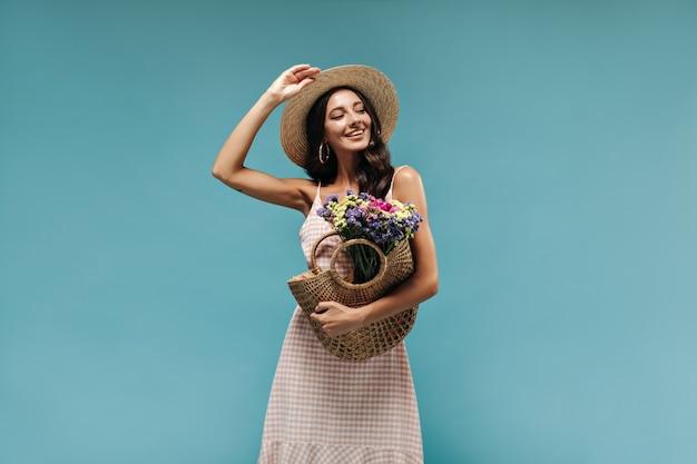 Fröhliche moderne brünette mit ohrringen und coolem hut im stilvollen leichten kleid posiert mit strohhandtasche und bunten blumen