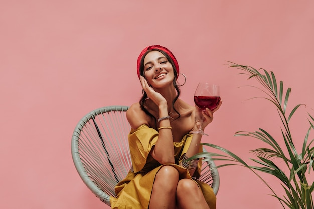 Fröhliche moderne frau mit brünetten haaren in accessoires und hellem, coolem kleid, die auf einem stuhl sitzt und an einer rosa wand lächelt