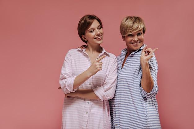 Fröhliche moderne frauen mit kurzer kühler frisur in gestreiften stilvollen kleidern, die lächeln und zeigen, um für text auf lokalisiertem hintergrund zu platzieren.