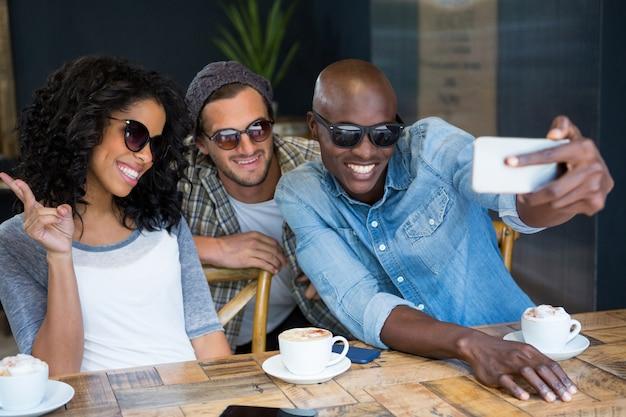 Fröhliche multiethnische freunde, die eine sonnenbrille tragen, während sie selfie im café nehmen