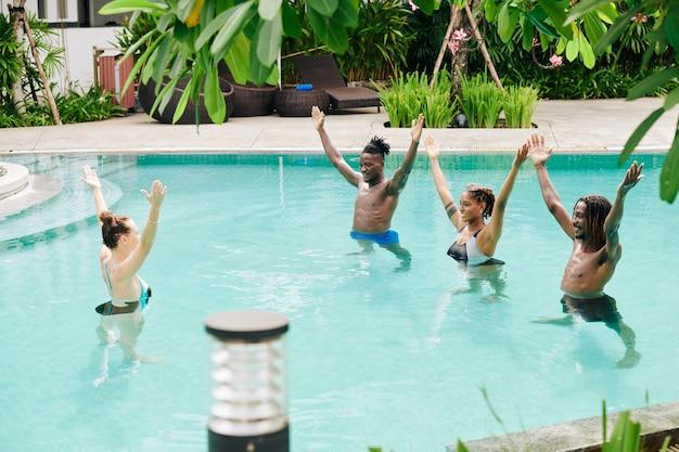 Fröhliche multiethnische junge leute, die sich nach dem wassergymnastik-trainer wiederholen, wenn sie im schwimmbad trainieren